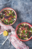 Kale, pomegranate and feta cheese tabbouleh in two bowls with spring onions and lemon mint dressing