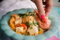 A woman garnishing moqueca (Brazilian fish stew) with prawns