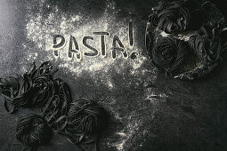 Frische Sepianudeln und das Wort 'Pasta' in Mehl geschrieben auf schwarzem Untergrund