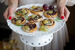 A woman serving mini pizzas with chevre, balsamic onions and grapes