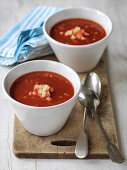 Bloody Mary Soup in two bowlsg rnished with chopped tomatoes