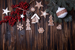 Christmas wooden background with branch of tree, holly berries, Christmas ball and gingerbread cookies