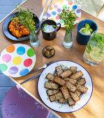 Gedeckter Campingtisch mit Mandeltofu, Süsskartoffelcreme und Oliven