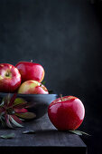 Fresh red apples on wooden table and in a bowl on dark background