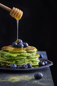 Honey pouring from wooden spoon to tasty green pancakes with blueberry