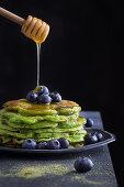 Honig tropft auf grüne Pancakes mit Heidelbeeren