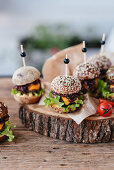 Small meat burgers with fresh salad on a wooden plate