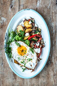 Fried vegetables with potatoes and fried egg