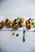 Grilled baguette slices with a vegan spread, grapes, yellow tomatoes and basil