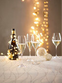Champagne glasses in front of glowing fairy lights