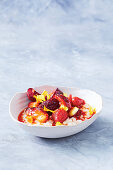 Pearl couscous pudding with coconut milk, strawberries and plums