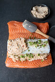 A raw salmon fillet spread with shrimp cream and topped with a cod fillet