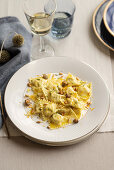 Triangoli with ricotta and anchovy stuffing, deep-fried pine nuts and capers
