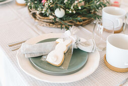 Place setting with bunny biscuit in gift bag on table set for Easter