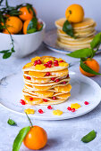 Pancakes with tangerines, pomegranate seeds and maple syrup
