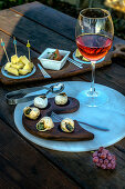 A glass of pink wine and appetizers - snails and cheese with chutney on a wooden table outdoors