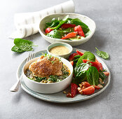 Portion of chicken leg with spinach and salad