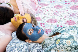 Women laying down with colourful face masks