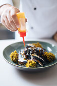 A chef drizzling cooked mussels with sauce