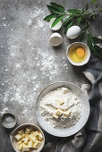 Flat lay of beautiful arrangement with bowl of flour and butter with eggs on marble table with green branch