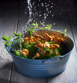 Chanterelles on moss in a vintage enamel container with a water splash