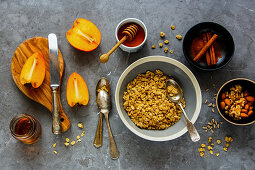 Healthy breakfast variety of cinnamon granola, fresh persimmon, maple syrup, honey and nuts