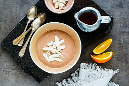 Maple syrup, orange fruit and chocolate yogurt bowl with coconut chips