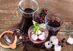 Homemade elderberry juice in glasses and carafes with ice cubes and mint