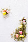 An Easter nest with coloured chicken eggs and quail's eggs