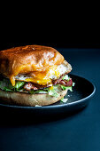 A burger with fried egg and ham