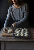 Crop human holding tray with set of beignets and flour