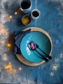 A Christmas place setting on a blue background with light decorations