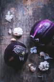 Round eggplants and garlic on a wooden surface