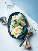 Hard-boiled eggs with a caper sauce on a bed of mashed potatoes