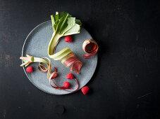Fresh rhubarb strips and raspberries on a plate