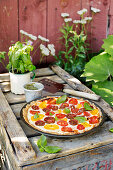 A colourful tomato tart on a rustic wooden crate