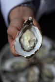 A person holding a freshly opening oyster