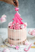 Tall layer cake with cranberry buttercream decorated with meringues and Christmas cookies
