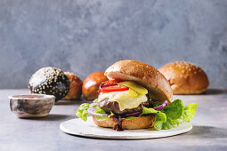 Homemade classic and mini burgers in wheat and black buns with beef and veal cutlets, melted cheese and vegetables
