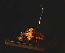 Tasty hot fried chicken with sharp knife placed on tray on black background