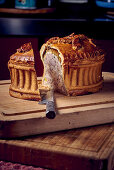 Puff pastry pie on a wooden cutting board, sliced