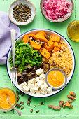 Buddha bowl (vegan) with red lentils, sweet potatoes, tofu, eggplant and greens, ajvar