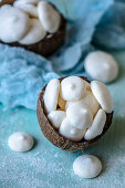 Meringue from aquafabs in a coconut shell on a blue background