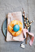Yeast dough wreath with a blue coloured egg and pussy willow