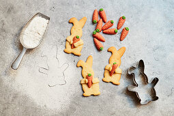 Easter Bunny biscuits with marzipan carrots, cookie cutter and a scoop with flour