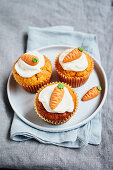 Carrot muffins topped with cream cheese frosting and marzipan carrots