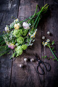 Tying an Easter bouquet of viburnum, freesias and ranunculus
