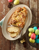 A bread plait with flaked almonds and coloured Easter eggs in a wire basket