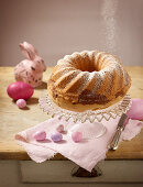 A marble Bundt cake dusted with icing sugar with Easter decorations