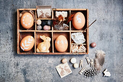 Brown Easter eggs with white motifs and Easter decorations in display case